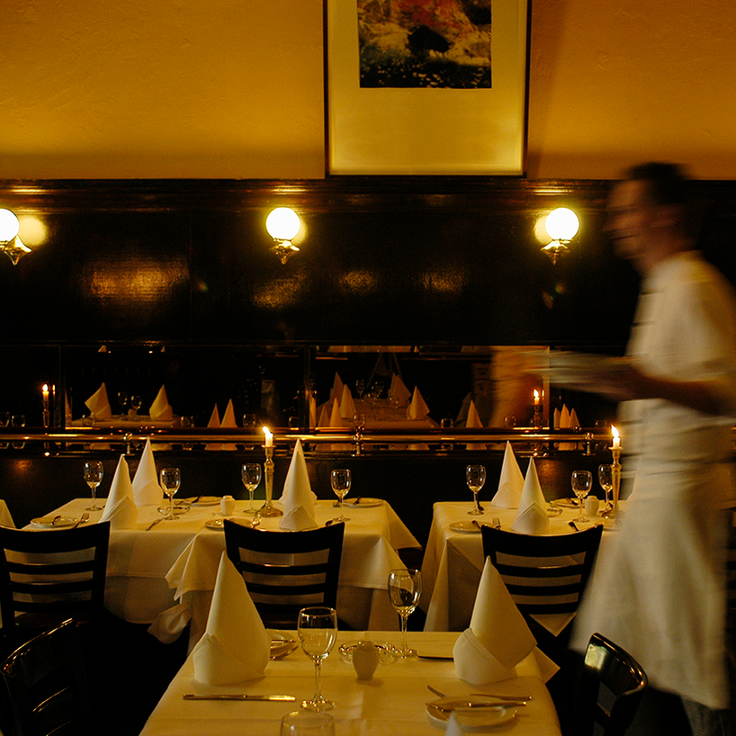 Restaurant seating with table set with candles and waiter walking by